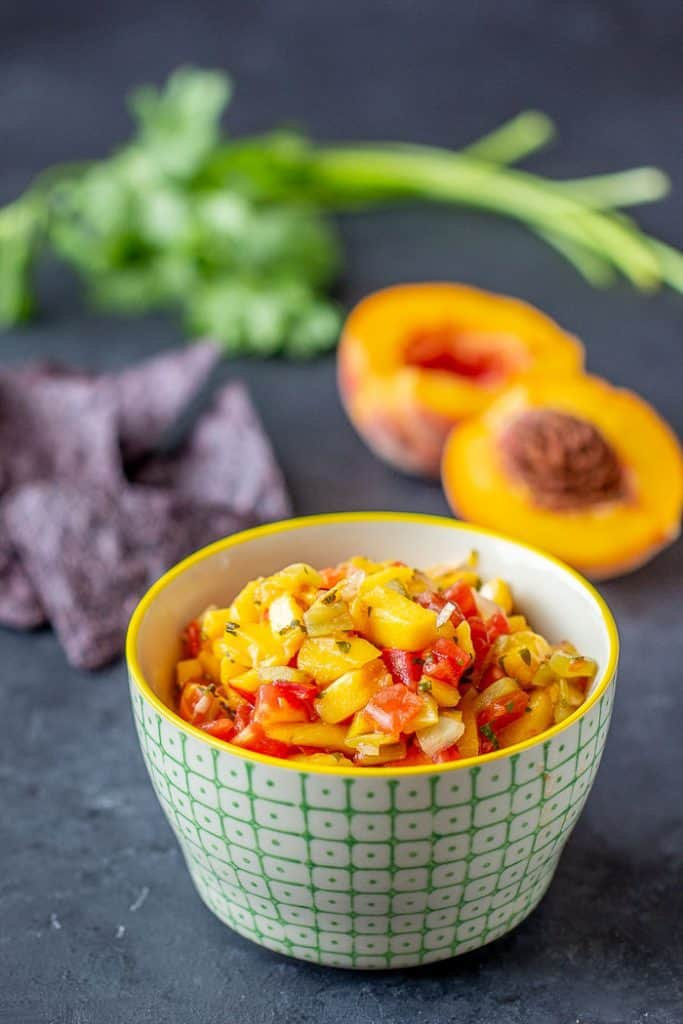 Roasted hatch peach salsa gives you spicy-sweet flavor that goes will with chicken, fish, pork, or just chips. Preserve it so you have the taste of summer all year long.