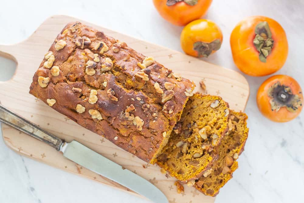 Pumpkin persimmon bread sliced overhead with knife