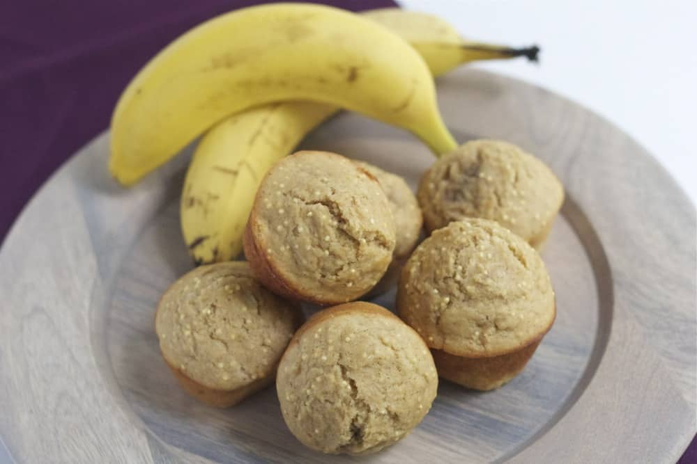 Banana millet muffins on a plate with bananas