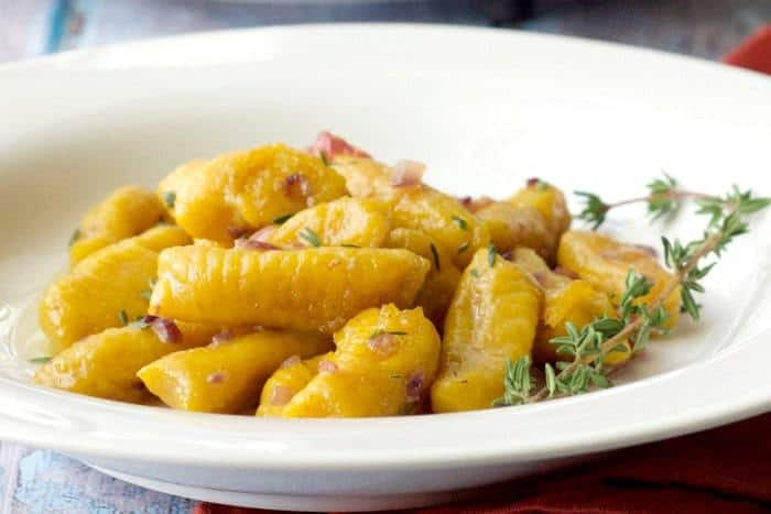 Pumpkin Gnocchi is tossed with a sauce of butter, shallots, bacon, and fresh herbs.