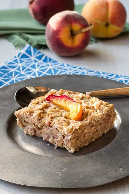 baked peach oatmeal slice on a silver plate