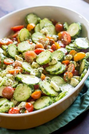 Cucumber tomato salad has fresh pesto as the dressing for a dish full of summer garden flavor.