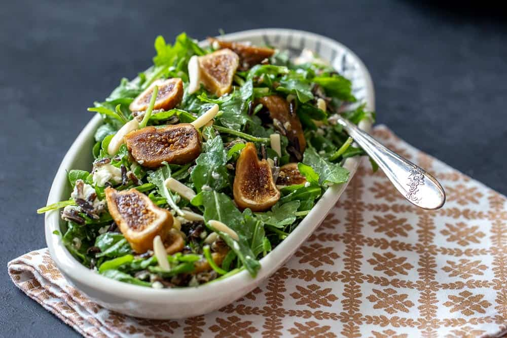 Fig wild rice salad with arugula in a bowl