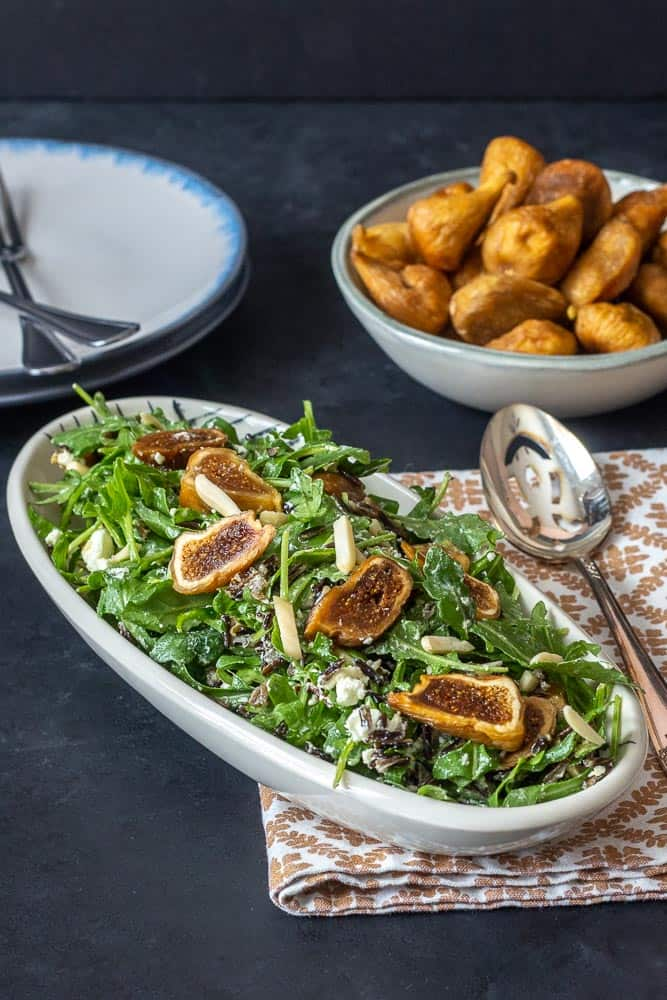 Salad with arugula, dried figs, and almonds, with plates and bowls
