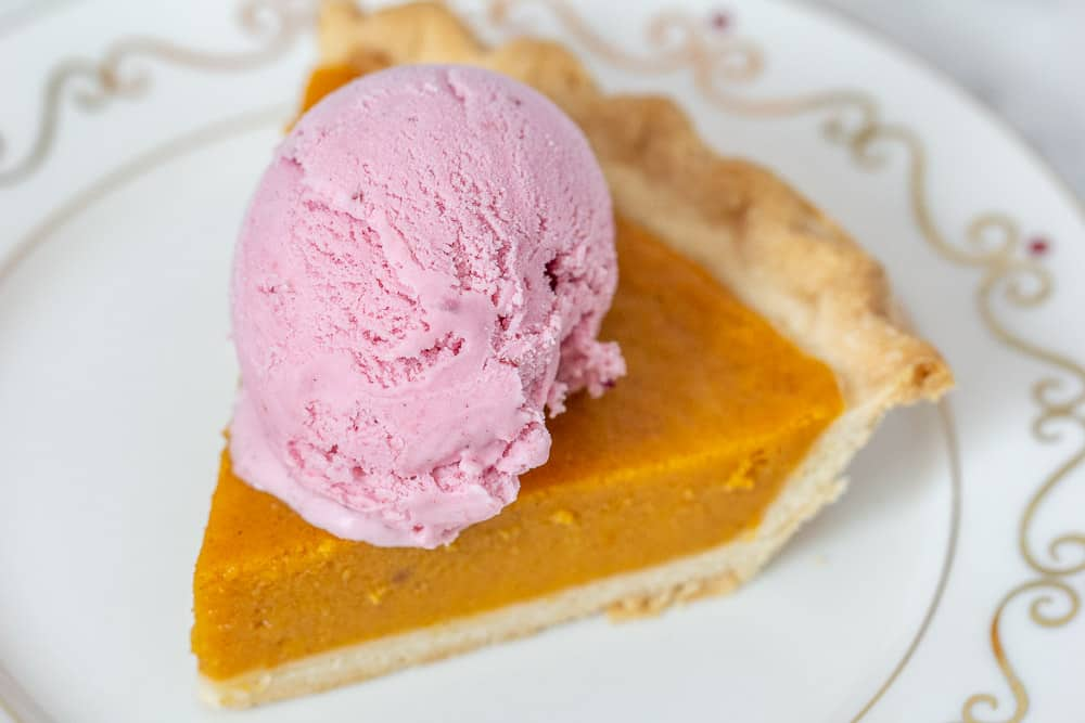 Slice of pumpkin pie with cranberry ice cream on top