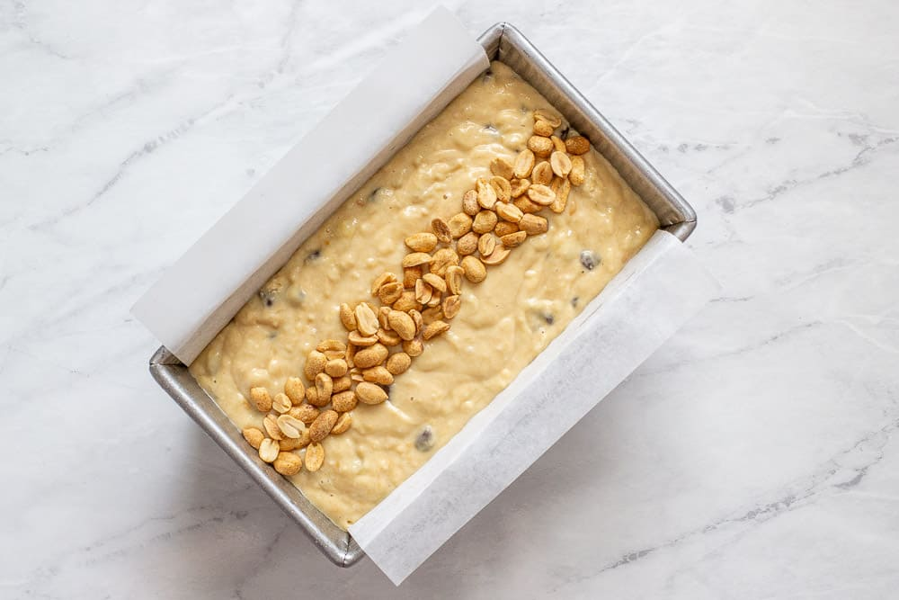 unbaked banana bread with peanuts on top