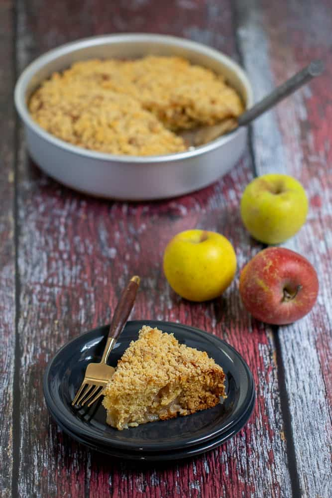 Apple coffee cake with a slice on a plate and apples