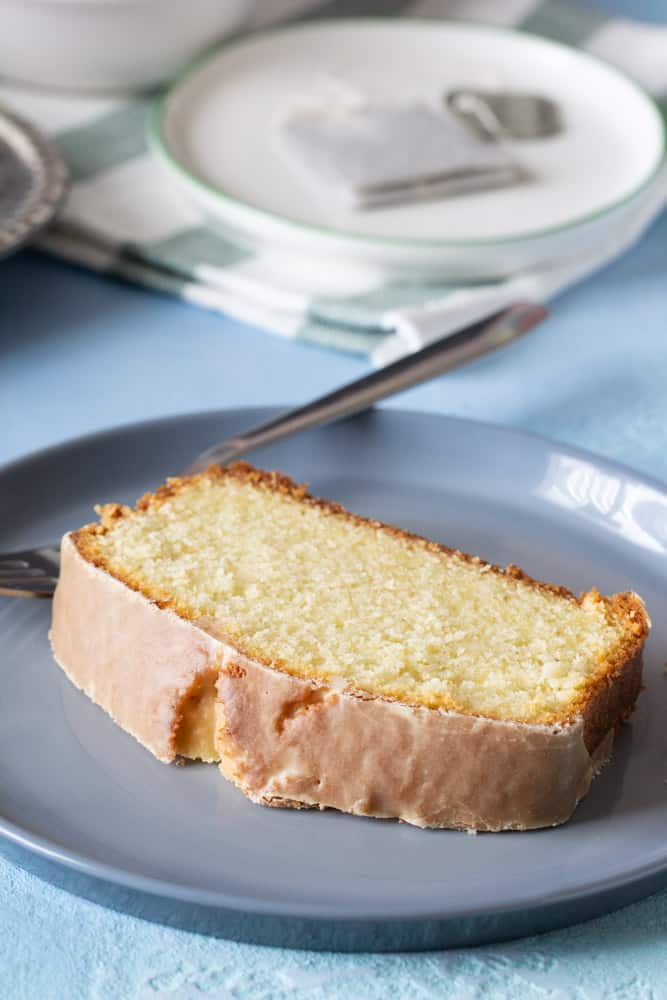 slice of cardamom cake with fork on grey plate