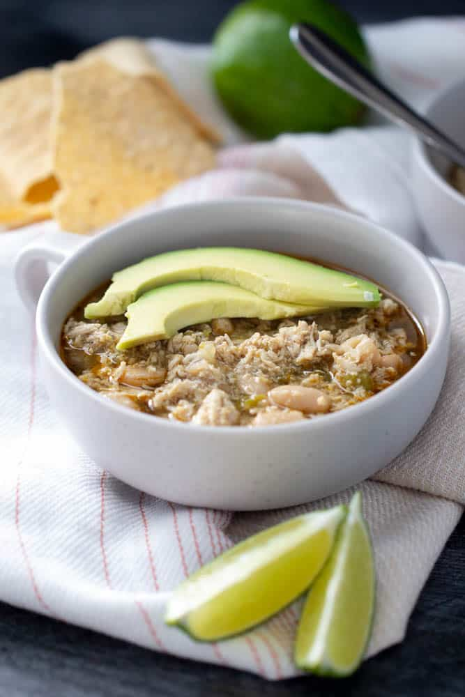 white bean chicken chili with avocado and lime in a bowl
