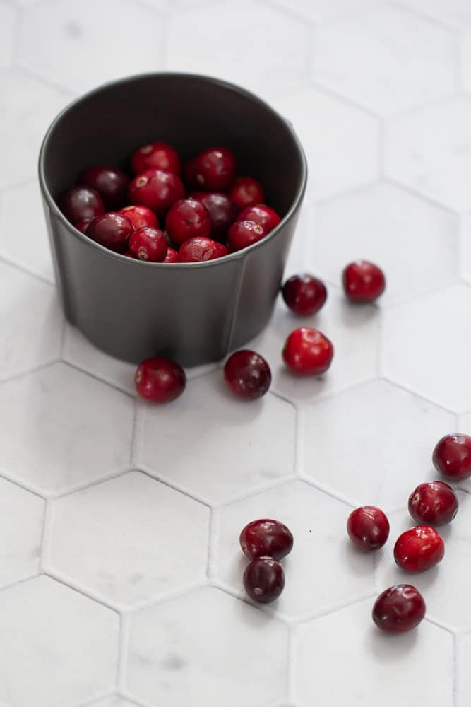 cranberries in black bowl with some loose on table