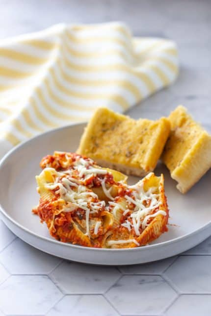 stuffed pasta shells with chicken on a plate with garlic bread slices