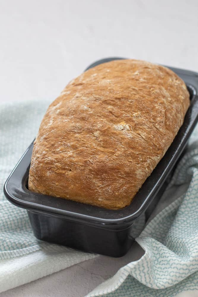 baked honey oatmeal bread in a black ceramic loaf pan