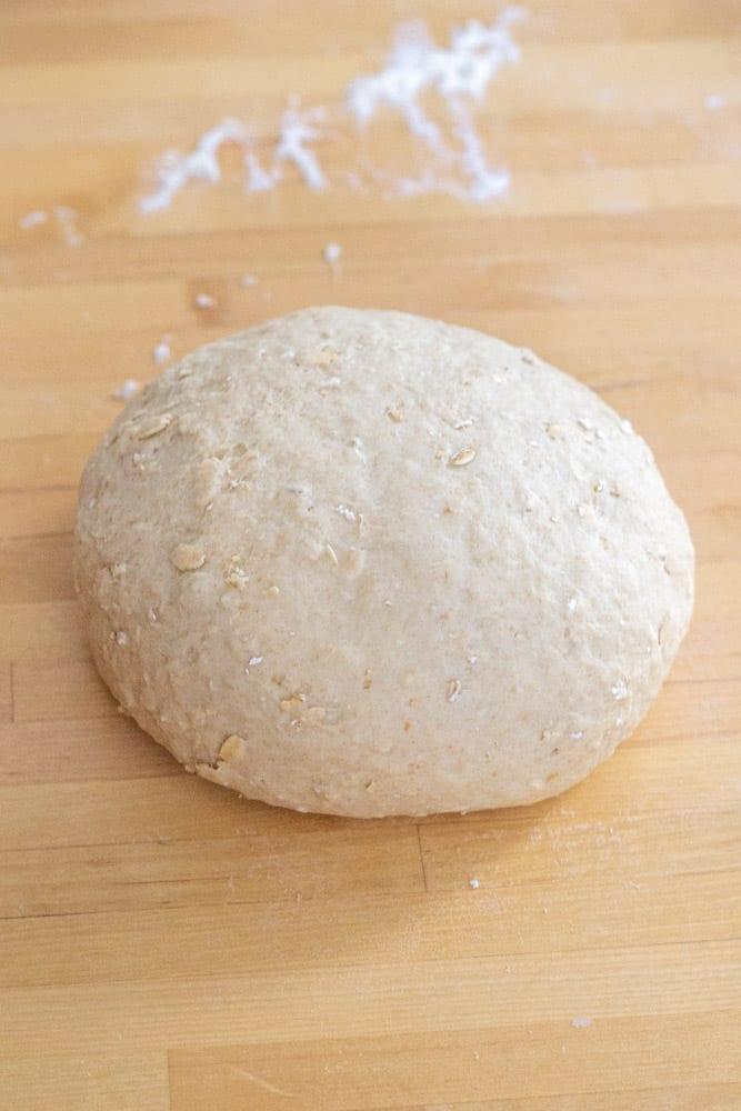 honey oatmeal bread dough on a wooden countertop