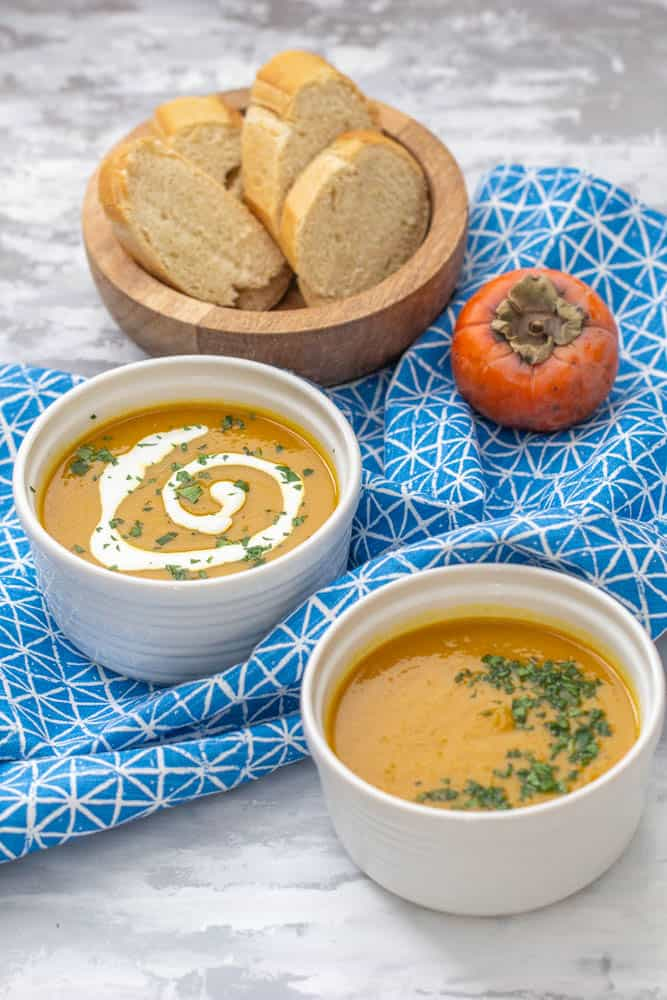 persimmon soup in two bowls with a bowl of bread