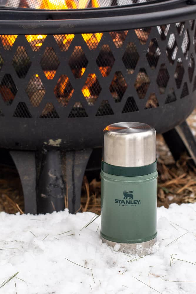 green Stanley food jar next to a fire pit in the snow