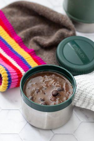 black bean soup in stanley food jar with colorful wool hat behind