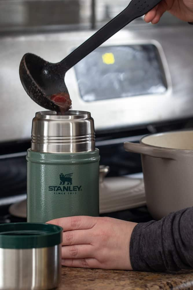 ladle pouring soup into green Stanley food jar on a kitchen counter