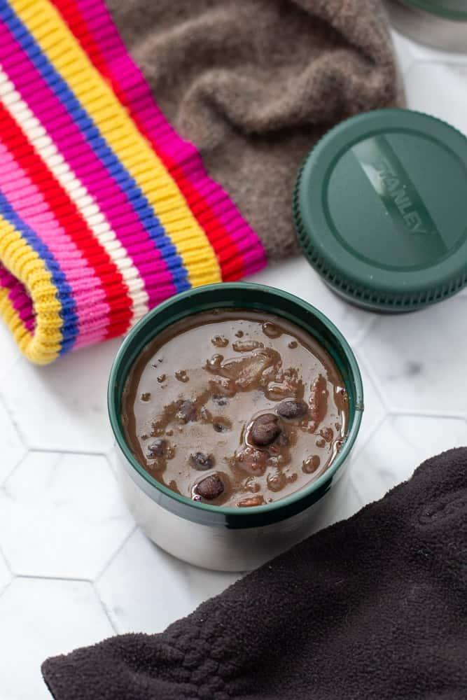black bean soup in stanley food jar overhead, with winter gear beside