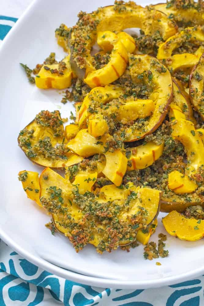 roasted winter squash with garlic herb topping on a platter with a blue and white napkin