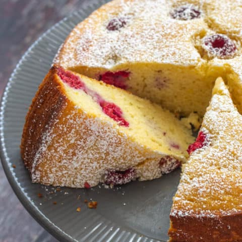 close up of sliced ricotta cake with raspberries and lemon on a gray cake plate