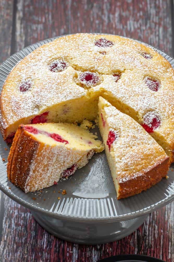 sliced ricotta cake with raspberries and lemon on a gray cake plate