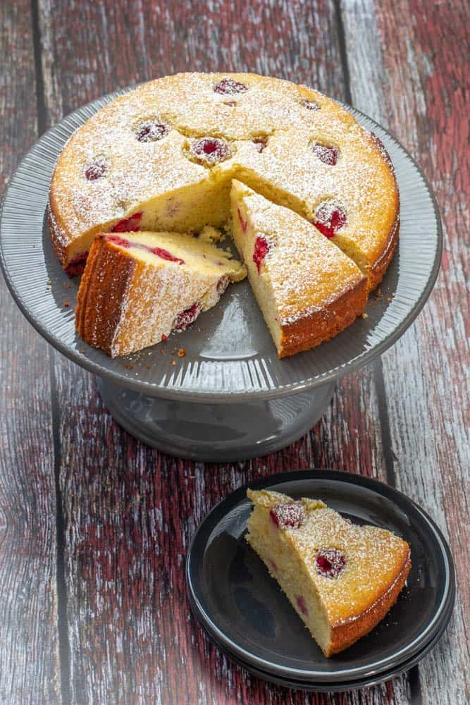 sliced ricotta cake with raspberries and lemon on a gray cake plate with a slice off to the side on a black plate