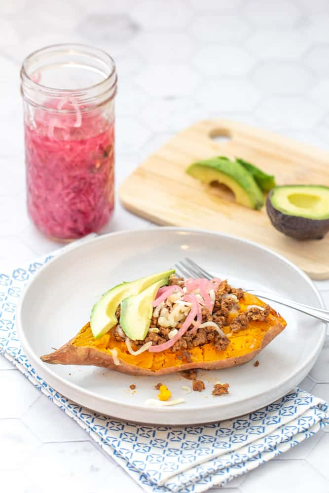 sweet potato topped with meat, cheese and other toppings on a plate with a decorative napkin