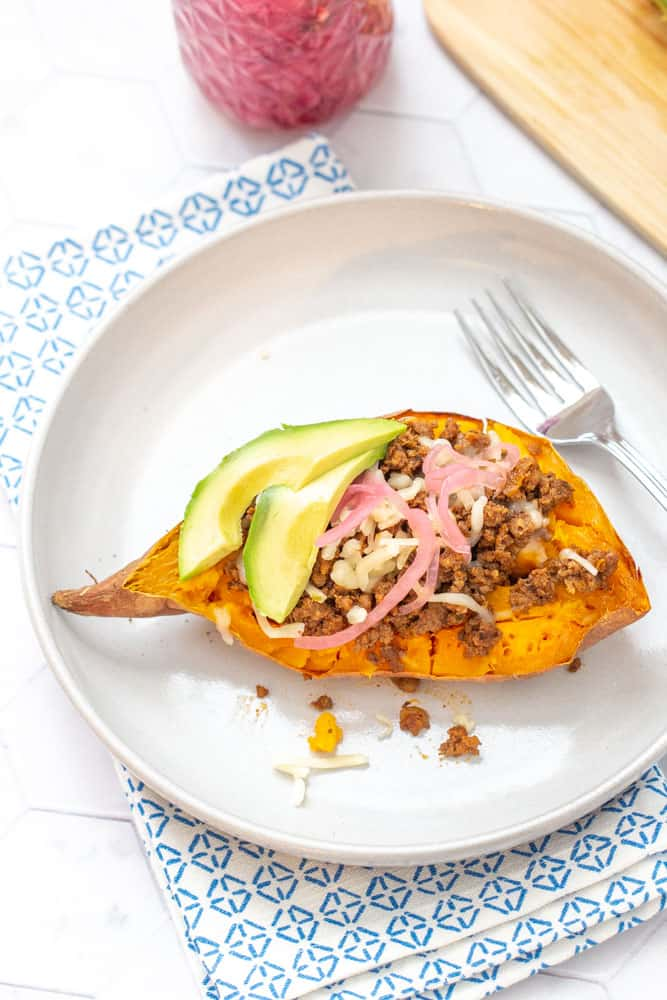 overhead of sweet potato topped with meat, cheese and other toppings on a plate with a decorative napkin