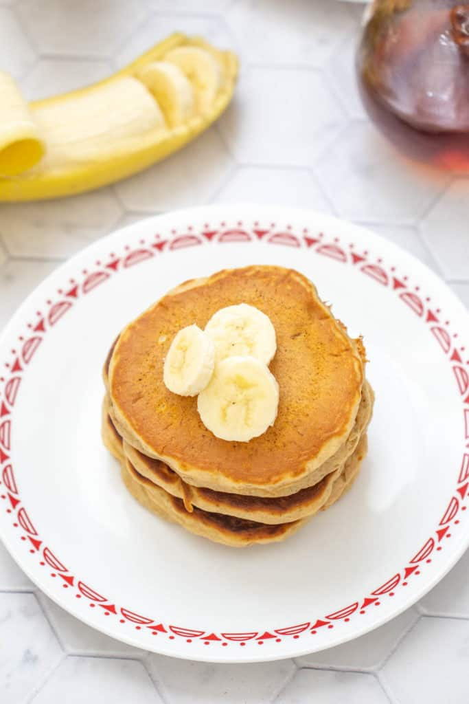 overhead of banana bread pancakes with banana slices on top
