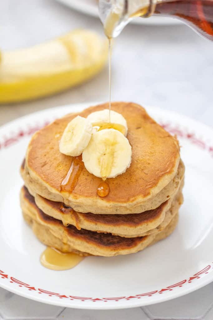 syrup being poured onto banana bread pancakes