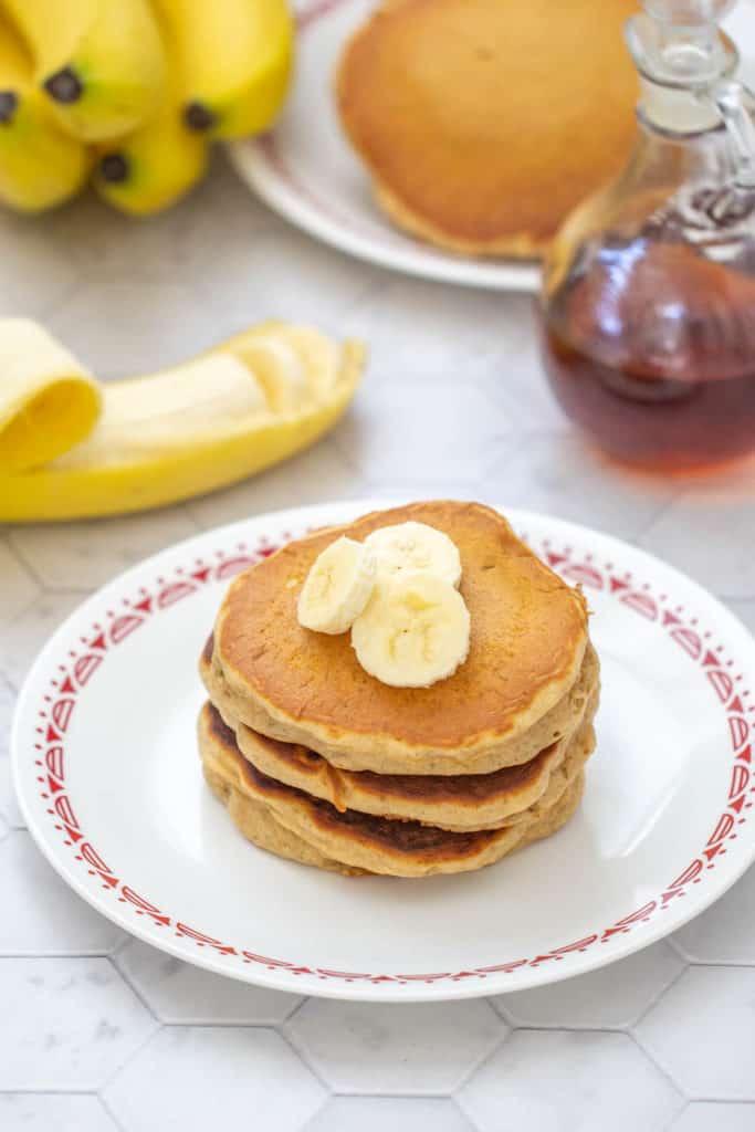 banana bread pancakes with bananas on top, banana and syrup behind