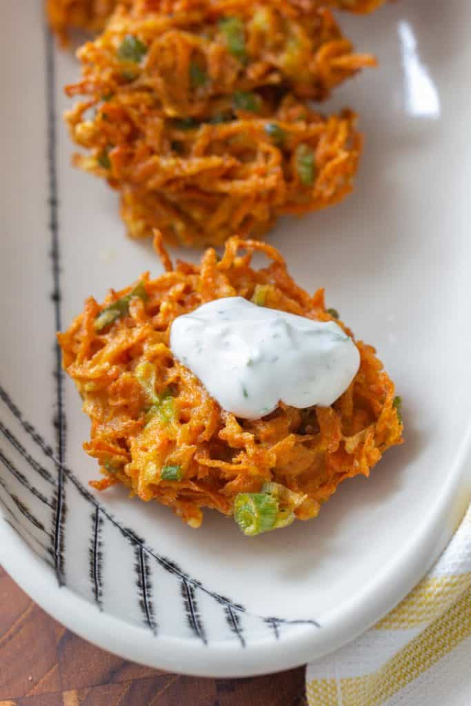 close up of carrot fritter with yogurt sauce on top