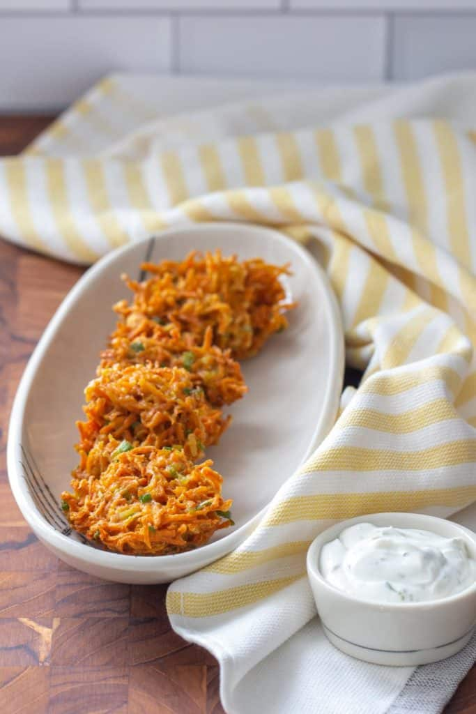 carrot fritters on a white plate with a yellow napkin and a white bowl of dill sauce