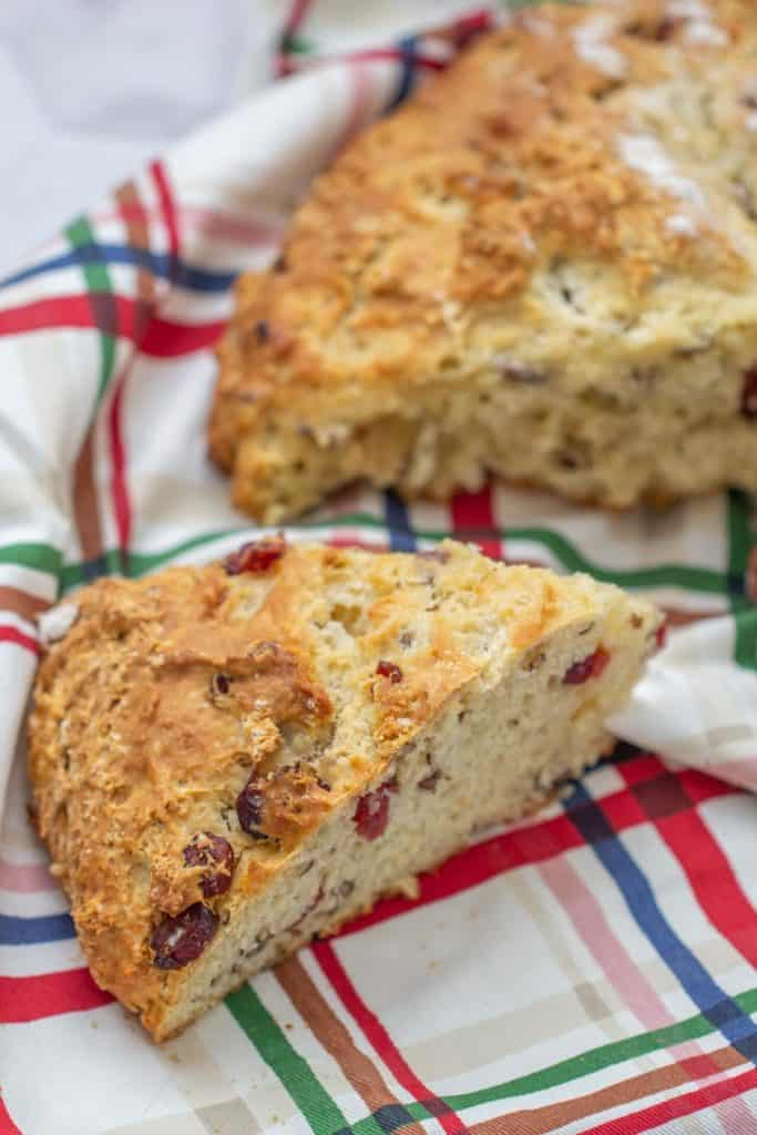slice of cranberry soda bread with pecans on a plaid kitchen towel