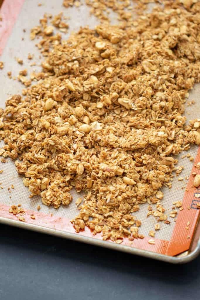 peanut butter granola on a silicone liner on a sheet pan
