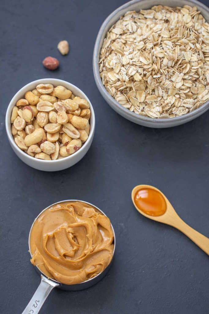 ingredients for peanut butter granola on a black background