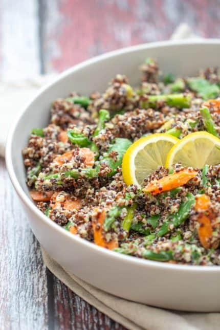 gray serving dish of quinoa primavera with lemon slices on top