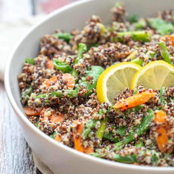 gray serving dish of quinoa primavera with lemon slices on top