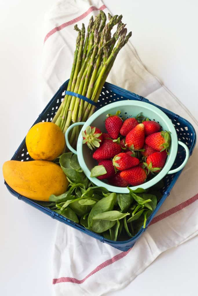 spinach, strawberries, mango, and asparagus in a blue wicker basket