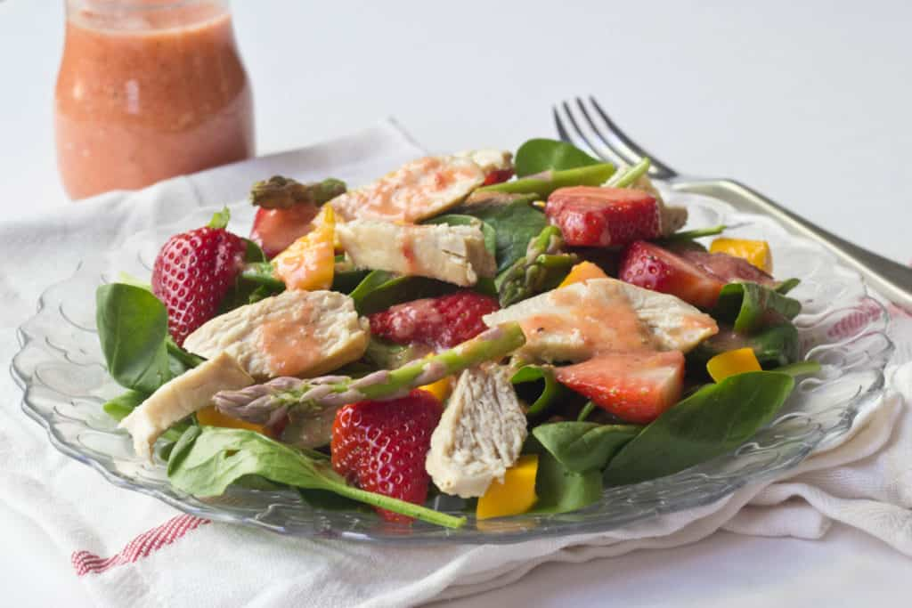strawberry, spinach, and chicken salad on a glass plate