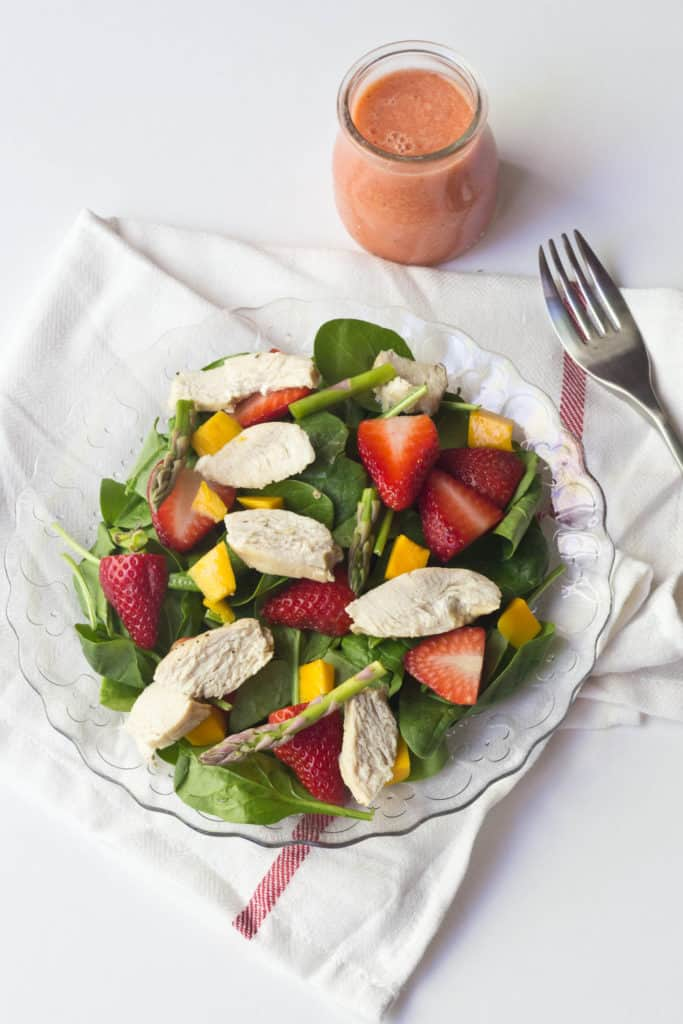overhead of a chicken salad with strawberries, mango, and asparagus on a glass plate