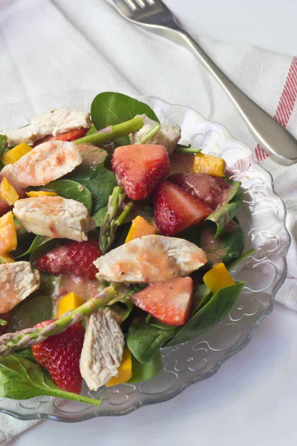 close up of a salad with chicken, fruit, and citrus dressing on a glass plate