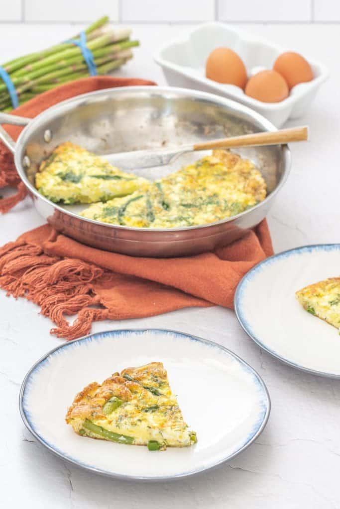sliced asparagus dill frittata on white plates with serving pan