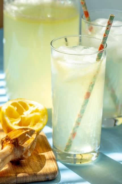 glasses of lemonade with paper straws and a citrus reamer beside
