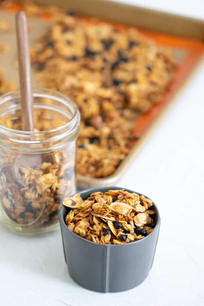 lemon blueberry granola in a gray bowl with a jar and sheet pan behind