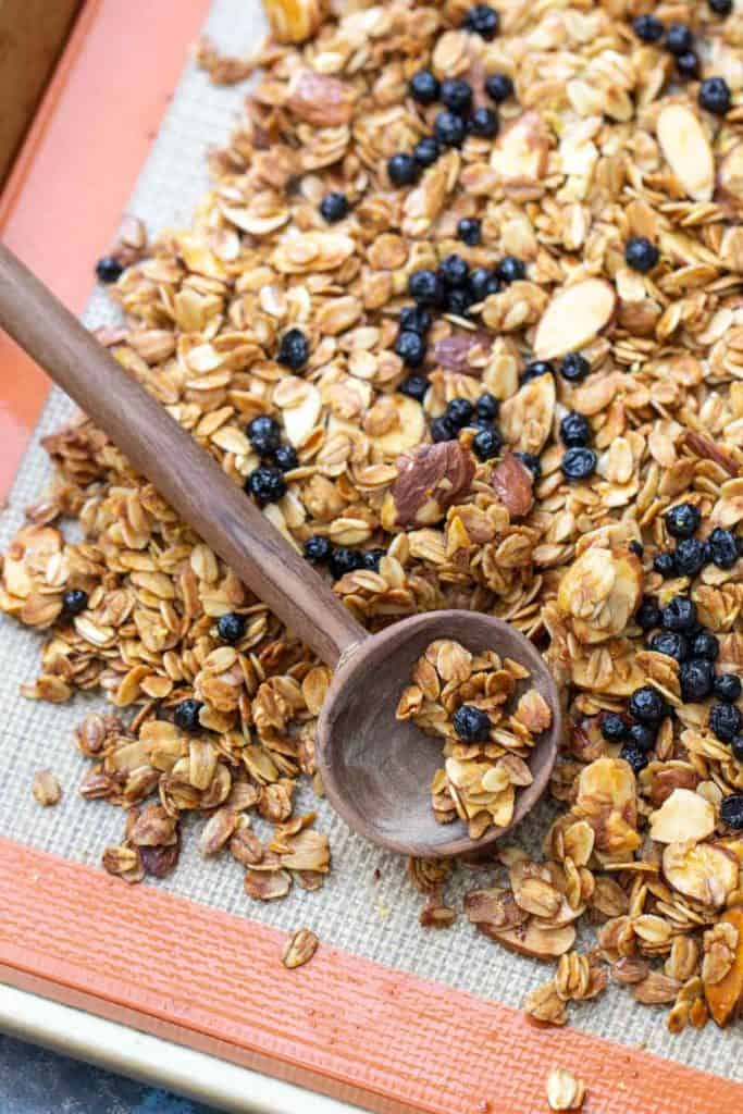 sheet pan of lemon blueberry granola with a wooden spoon