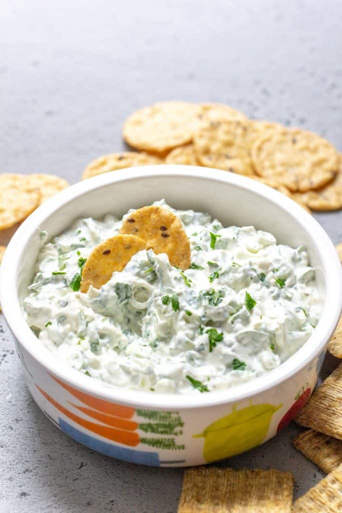 bowl of green onion dip with crackers
