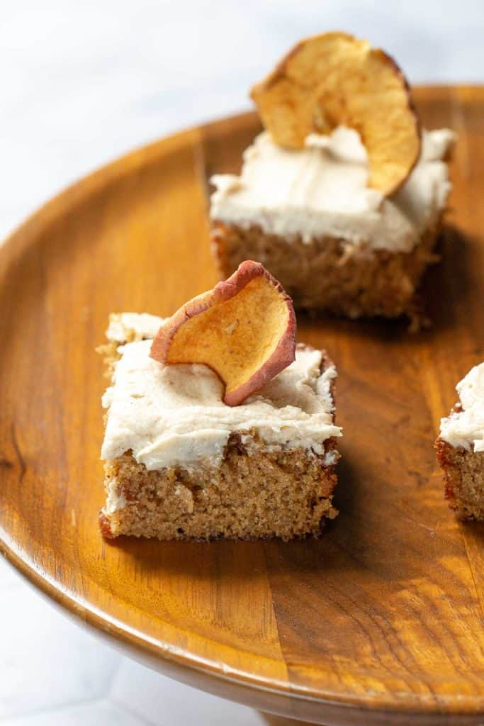 pieces of apple spice cake with brown butter frosting and apple chips on top