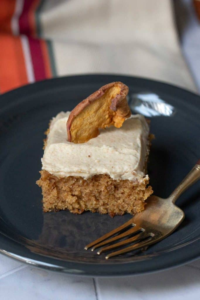 square of apple spice cake on black plate with fork