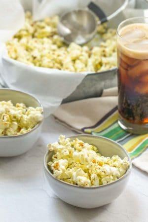 bowls of pesto popcorn with a soda